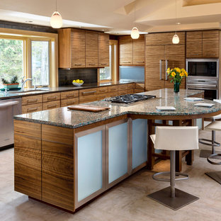 This is an example of a contemporary l-shaped kitchen in Milwaukee with an undermount sink, flat-panel cabinets, medium wood cabinets, recycled glass benchtops, black splashback, ceramic splashback, stainless steel appliances, linoleum floors and with island.