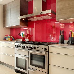 Moderne Küche mit flächenbündigen Schrankfronten, beigen Schränken, Küchenrückwand in Rot, Glasrückwand und Küchengeräten aus Edelstahl in Buckinghamshire
