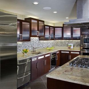 Cette image montre une petit cuisine ouverte design en L avec un électroménager en acier inoxydable, un placard à porte vitrée, des portes de placard en bois sombre, un plan de travail en granite, une crédence en carreau de verre, un sol en carrelage de porcelaine, un îlot central, une crédence multicolore, un évier encastré, un sol gris et un plan de travail vert.
