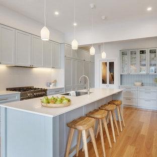 Mittelgroße Maritime Küche mit Waschbecken, Schrankfronten im Shaker-Stil, grauen Schränken, Mineralwerkstoff-Arbeitsplatte, Küchenrückwand in Weiß, Küchengeräten aus Edelstahl, Kücheninsel, weißer Arbeitsplatte, hellem Holzboden und beigem Boden in Sydney