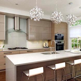 トロントの中サイズのコンテンポラリースタイルのおしゃれなキッチン (シングルシンク、フラットパネル扉のキャビネット、ベージュのキャビネット、珪岩カウンター、ガラス板のキッチンパネル、シルバーの調理設備の、淡色無垢フローリング、茶色い床、白いキッチンカウンター) の写真