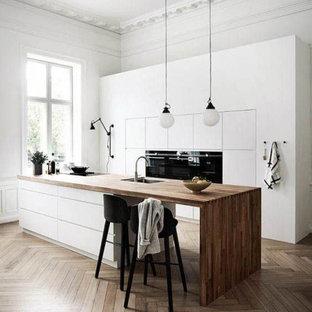 コロンバスの中くらいのコンテンポラリースタイルのおしゃれなキッチン (アンダーカウンターシンク、フラットパネル扉のキャビネット、白いキャビネット、木材カウンター、グレーのキッチンパネル、黒い調理設備、無垢フローリング、茶色い床、茶色いキッチンカウンター) の写真