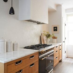 コロンバスの小さいコンテンポラリースタイルのおしゃれなキッチン (アンダーカウンターシンク、ルーバー扉のキャビネット、中間色木目調キャビネット、大理石カウンター、白いキッチンパネル、シルバーの調理設備の、淡色無垢フローリング、グレーの床、白いキッチンカウンター) の写真