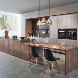 コロンバスの広いコンテンポラリースタイルのおしゃれなキッチン (アンダーカウンターシンク、フラットパネル扉のキャビネット、グレーのキャビネット、グレーのキッチンパネル、グレーのキッチンカウンター、珪岩カウンター、石スラブのキッチンパネル、黒い調理設備、セラミックタイルの床、グレーの床) の写真