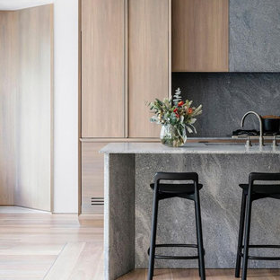 Design ideas for a mid-sized contemporary single-wall open plan kitchen in Columbus with an undermount sink, beaded inset cabinets, medium wood cabinets, concrete benchtops, grey splashback, stone slab splashback, stainless steel appliances, light hardwood floors, with island, brown floor and grey benchtop.