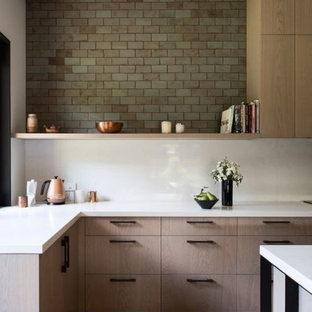 Design ideas for a medium sized contemporary l-shaped open plan kitchen in Columbus with a submerged sink, flat-panel cabinets, light wood cabinets, quartz worktops, green splashback, terracotta splashback, stainless steel appliances, light hardwood flooring, an island, brown floors and white worktops.