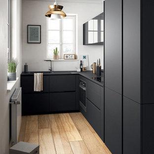 Réalisation d'une petite cuisine design en L fermée avec un évier encastré, un placard à porte plane, des portes de placard noires, un plan de travail en quartz, un électroménager noir, un sol en bois clair, un sol marron et un plan de travail noir.