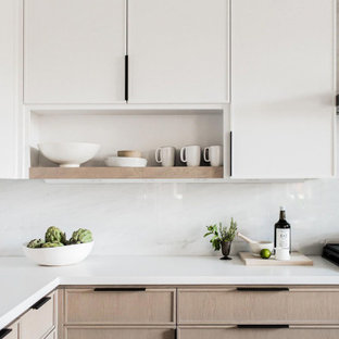 Foto på ett avskilt, mellanstort funkis vit l-kök, med en undermonterad diskho, luckor med profilerade fronter, skåp i ljust trä, marmorbänkskiva, svart stänkskydd, stänkskydd i marmor, svarta vitvaror, ljust trägolv och brunt golv