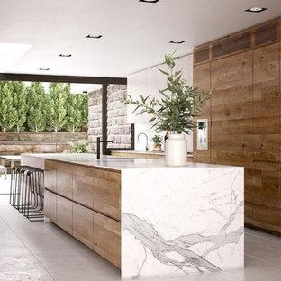 コロンバスの大きいコンテンポラリースタイルのおしゃれなキッチン (アンダーカウンターシンク、フラットパネル扉のキャビネット、淡色木目調キャビネット、大理石カウンター、シルバーの調理設備の、セメントタイルの床、グレーの床、白いキッチンカウンター) の写真