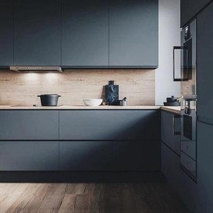 コロンバスの広いコンテンポラリースタイルのおしゃれなキッチン (アンダーカウンターシンク、フラットパネル扉のキャビネット、青いキャビネット、木材カウンター、茶色いキッチンパネル、木材のキッチンパネル、シルバーの調理設備、無垢フローリング、茶色い床、茶色いキッチンカウンター) の写真