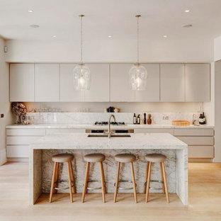 Inspiration för ett mycket stort funkis vit vitt kök, med en undermonterad diskho, släta luckor, grå skåp, marmorbänkskiva, vitt stänkskydd, stänkskydd i marmor, rostfria vitvaror, ljust trägolv, en köksö och brunt golv