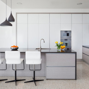Large industrial l-shaped eat-in kitchen in Perth with an integrated sink, flat-panel cabinets, solid surface benchtops, grey splashback, mosaic tile splashback, stainless steel appliances, terrazzo floors, with island, beige floor and black benchtop.