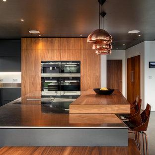 Große Moderne Wohnküche mit flächenbündigen Schrankfronten, hellbraunen Holzschränken, Edelstahl-Arbeitsplatte, Elektrogeräten mit Frontblende, Betonboden, Kücheninsel und grauem Boden in Cornwall