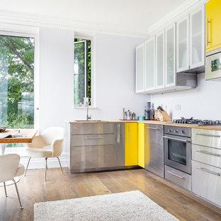 Exempel på ett modernt kök, med en nedsänkt diskho, släta luckor, skåp i rostfritt stål, träbänkskiva, rostfria vitvaror och ljust trägolv