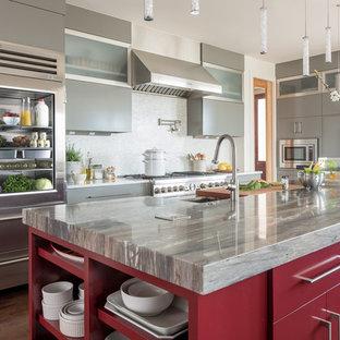 Diseño de cocina actual, cerrada, con fregadero bajoencimera, armarios con paneles lisos, puertas de armario rojas, salpicadero verde, electrodomésticos de acero inoxidable, una isla y suelo marrón