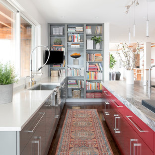 Photo of a contemporary galley kitchen in Denver with a belfast sink, flat-panel cabinets, red cabinets, dark hardwood flooring, an island and brown floors.