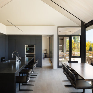 Photo of a medium sized contemporary l-shaped kitchen/diner in Denver with an integrated sink, flat-panel cabinets, black cabinets, granite worktops, white splashback, stainless steel appliances, medium hardwood flooring and an island.