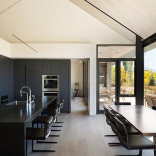 デンバーの中サイズのコンテンポラリースタイルのおしゃれなキッチン (一体型シンク、フラットパネル扉のキャビネット、黒いキャビネット、御影石カウンター、白いキッチンパネル、シルバーの調理設備、無垢フローリング) の写真