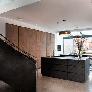 Modern inredning av ett stort kök, med en integrerad diskho, släta luckor, skåp i ljust trä, bänkskiva i kvartsit, kalkstensgolv, flera köksöar och integrerade vitvaror