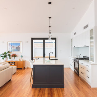 Design ideas for a transitional galley open plan kitchen in Newcastle - Maitland with a drop-in sink, shaker cabinets, white cabinets, black appliances, medium hardwood floors, with island, brown floor and grey benchtop.