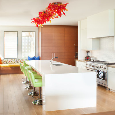 Open concept kitchen - mid-sized contemporary u-shaped light wood floor open concept kitchen idea in Los Angeles with an undermount sink, flat-panel cabinets, white cabinets, white backsplash, stainless steel appliances, an island, solid surface countertops and ceramic backsplash