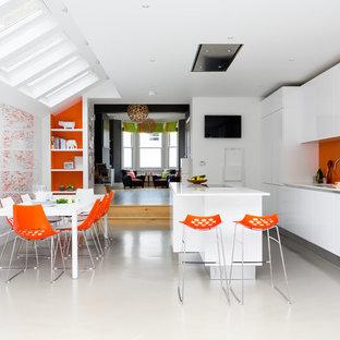 Contemporary open concept kitchen ideas - Open concept kitchen - contemporary galley open concept kitchen idea in London with flat-panel cabinets, white cabinets, orange backsplash, glass sheet backsplash, black appliances and an island