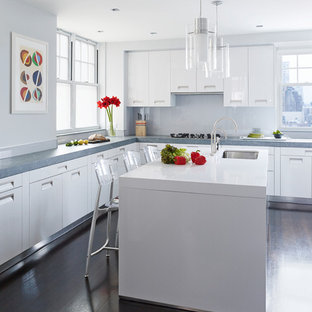 This is an example of a contemporary kitchen in New York with a submerged sink, flat-panel cabinets, white cabinets, concrete worktops, white splashback, dark hardwood flooring, an island and brown floors.