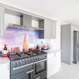 Huge contemporary open concept kitchen designs - Huge trendy u-shaped ceramic floor and gray floor open concept kitchen photo in London with an integrated sink, shaker cabinets, white cabinets, glass countertops, multicolored backsplash, glass sheet backsplash, black appliances, an island and green countertops