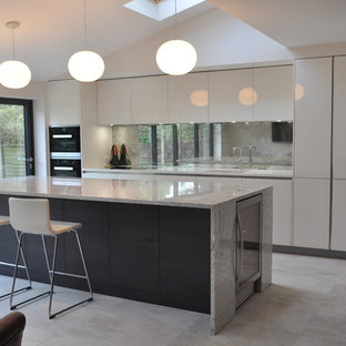 Ejemplo de cocina en L, contemporánea, abierta, con armarios con paneles lisos, salpicadero con efecto espejo, electrodomésticos de acero inoxidable, una isla y puertas de armario blancas