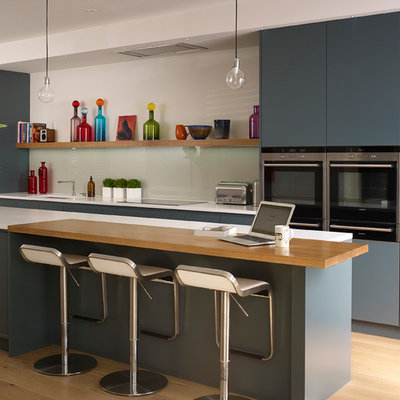 Kitchen - contemporary light wood floor kitchen idea in London with flat-panel cabinets, blue cabinets, white backsplash, stainless steel appliances and an island