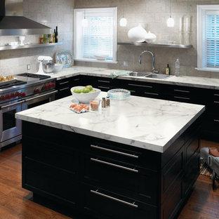 Ispirazione per una cucina minimal con lavello da incasso, elettrodomestici in acciaio inossidabile, ante nere e top in laminato