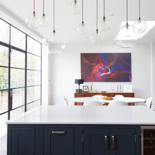 Photo of a medium sized contemporary open plan kitchen in London with a belfast sink, shaker cabinets, grey cabinets, quartz worktops, ceramic splashback, stainless steel appliances, dark hardwood flooring and an island.