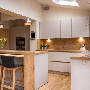 他の地域の中サイズのコンテンポラリースタイルのおしゃれなキッチン (フラットパネル扉のキャビネット、グレーのキャビネット、木材カウンター、ベージュキッチンパネル、木材のキッチンパネル、シルバーの調理設備の、淡色無垢フローリング、茶色い床、ベージュのキッチンカウンター) の写真