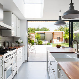 Design ideas for a medium sized contemporary galley open plan kitchen in London with a belfast sink, flat-panel cabinets, white cabinets, wood worktops, grey splashback, metro tiled splashback and an island.