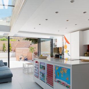 На фото: параллельная кухня в современном стиле с островом, врезной раковиной, плоскими фасадами, белыми фасадами, красным фартуком и фартуком из стекла с