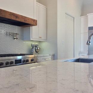 Große Moderne Wohnküche in U-Form mit Unterbauwaschbecken, Schrankfronten mit vertiefter Füllung, weißen Schränken, Quarzwerkstein-Arbeitsplatte, Küchenrückwand in Weiß, Rückwand aus Stäbchenfliesen, Küchengeräten aus Edelstahl, Porzellan-Bodenfliesen und Kücheninsel in Austin