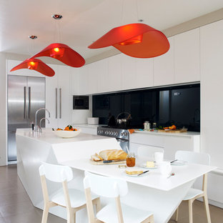 Example of a trendy kitchen design in London with flat-panel cabinets, white cabinets, black backsplash, glass sheet backsplash, stainless steel appliances and an island