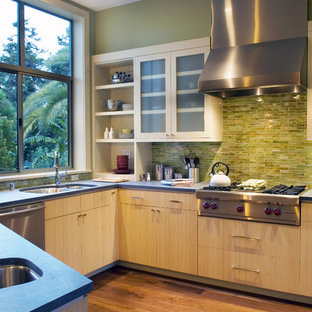 Example of a trendy kitchen design in San Francisco with a double-bowl sink, flat-panel cabinets, light wood cabinets, green backsplash and stainless steel appliances