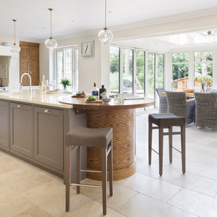Design ideas for a medium sized contemporary kitchen/diner in London with a double-bowl sink, recessed-panel cabinets, metallic splashback, mirror splashback, stainless steel appliances, limestone flooring and an island.