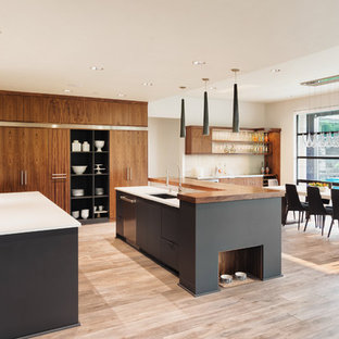 Large contemporary open concept kitchen ideas - Example of a large trendy l-shaped brown floor and light wood floor open concept kitchen design in Los Angeles with flat-panel cabinets, two islands, a single-bowl sink, medium tone wood cabinets, quartz countertops, white backsplash, stone slab backsplash and white appliances