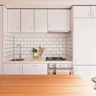 This is an example of a contemporary single-wall kitchen in Melbourne with a submerged sink, flat-panel cabinets, white cabinets, wood worktops, white splashback, metro tiled splashback, stainless steel appliances and an island.