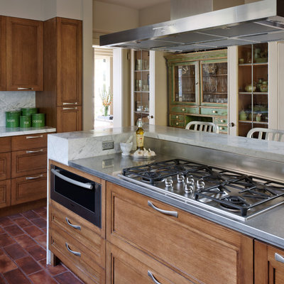Example of a trendy kitchen design in Seattle with stainless steel appliances, stainless steel countertops, recessed-panel cabinets, medium tone wood cabinets, white backsplash and stone slab backsplash