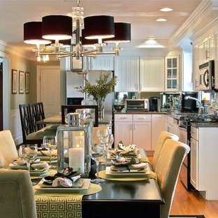 Eat-in kitchen - contemporary l-shaped eat-in kitchen idea in Boston with stainless steel appliances, recessed-panel cabinets, white cabinets and mirror backsplash