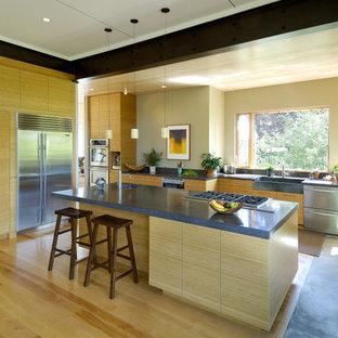 Inspiration för stora moderna kök med öppen planlösning, med bänkskiva i betong, en rustik diskho, släta luckor, beige skåp, rostfria vitvaror, bambugolv och en köksö