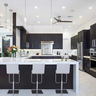 Photo of a large contemporary u-shaped kitchen in Miami with an undermount sink, black cabinets, marble benchtops, white splashback, stainless steel appliances, marble floors, a peninsula, flat-panel cabinets, white benchtop and beige floor.