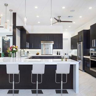マイアミの広いコンテンポラリースタイルのおしゃれなキッチン (アンダーカウンターシンク、黒いキャビネット、大理石カウンター、白いキッチンパネル、シルバーの調理設備、大理石の床、フラットパネル扉のキャビネット、白いキッチンカウンター、ベージュの床) の写真
