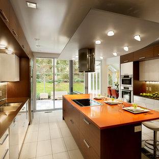 フィラデルフィアの大きいコンテンポラリースタイルのおしゃれなキッチン (ダブルシンク、フラットパネル扉のキャビネット、白いキャビネット、クオーツストーンカウンター、ベージュキッチンパネル、ガラスタイルのキッチンパネル、シルバーの調理設備の、磁器タイルの床、オレンジのキッチンカウンター) の写真