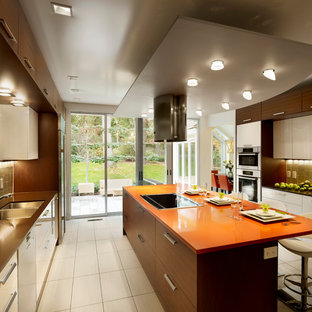 Inspiration for a large contemporary galley eat-in kitchen in Philadelphia with a double-bowl sink, flat-panel cabinets, white cabinets, quartz benchtops, beige splashback, glass tile splashback, stainless steel appliances, porcelain floors, with island and orange benchtop.