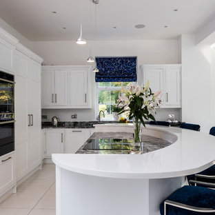 Inspiration for a classic l-shaped open plan kitchen in Hertfordshire with shaker cabinets, white cabinets, integrated appliances, an island, beige floors and grey worktops.