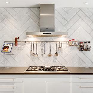 Удачное сочетание для дизайна помещения: отдельная, угловая кухня среднего размера в современном стиле с раковиной в стиле кантри, плоскими фасадами, белыми фасадами, столешницей из кварцевого композита, белым фартуком, техникой из нержавеющей стали, пробковым полом, островом, фартуком из каменной плитки и бежевым полом - самое интересное для вас